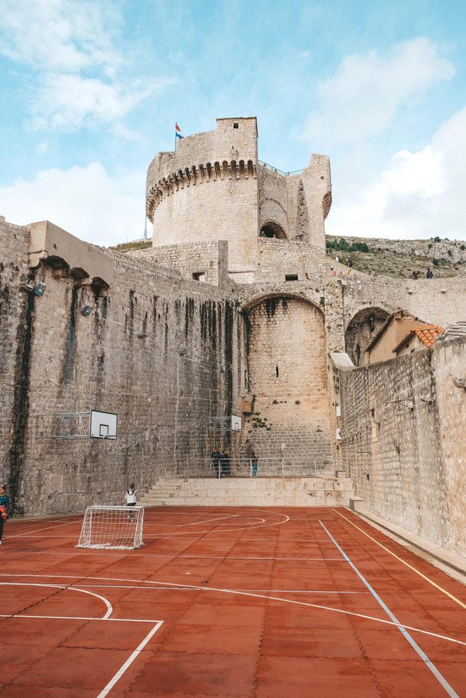 Terrain de basket au pied d'une tour des remparts