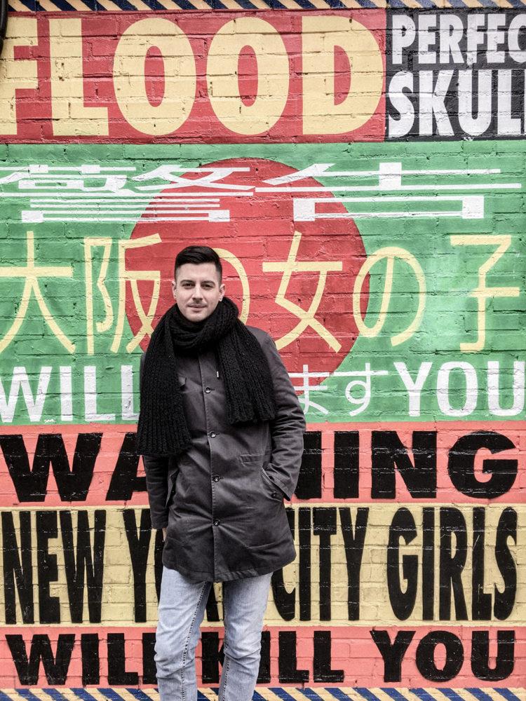 Nicolas contre un mur de street art publicitaire