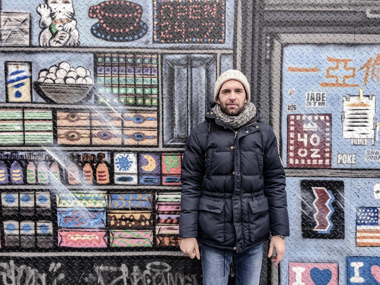 Julien contre la devanture d'une épicerie asiatique