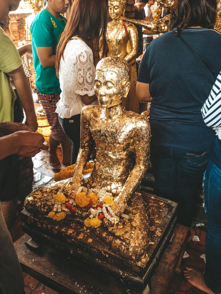 Les fidèles déposant des feuilles d'or