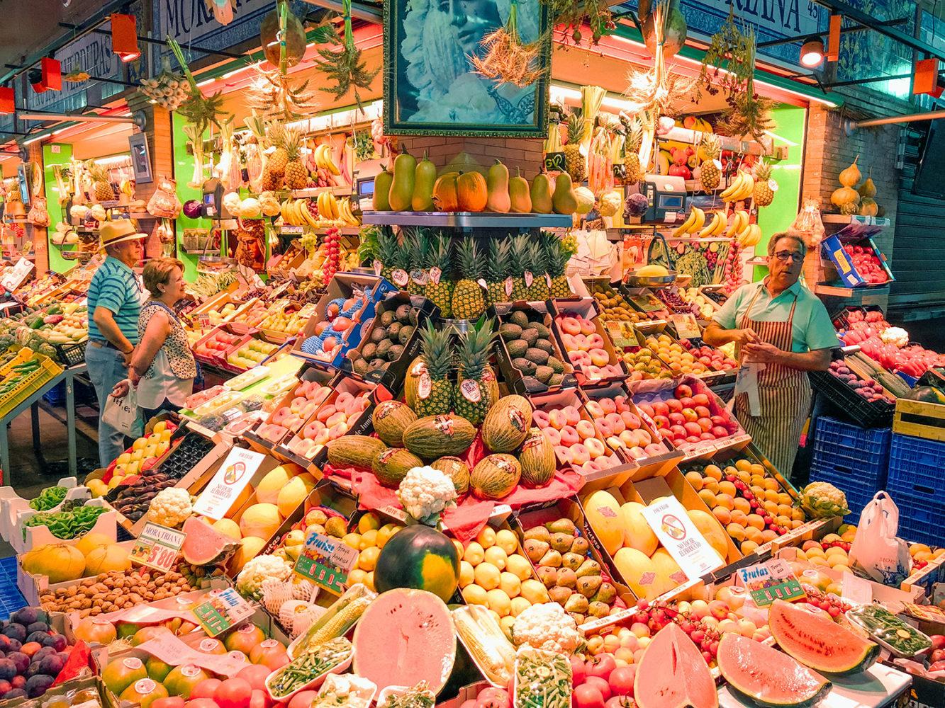 Primeur avec un étal de fruits et légumes colorés
